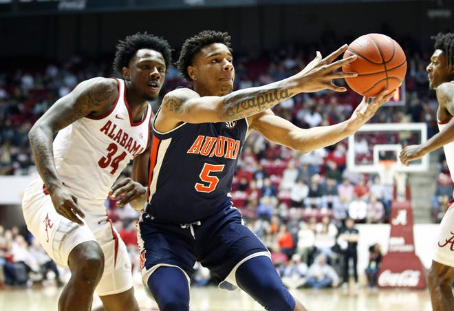 Auburn forward Chuma Okeke (5) reaches for the ball in front of Alabama guard Tevin Mack (34) during the first half at Coleman Coliseum on March 5, 2019.