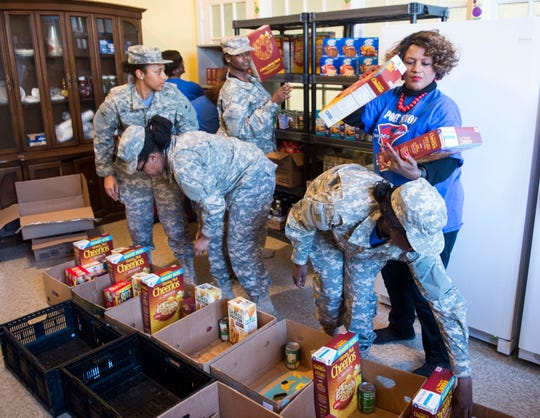 Parent Liaison Cubie Ray Hayes with the help of JROTC students loads boxes of foods in the food pantry at Lanier High School in Montgomery, Ala., on Tuesday, March 5, 2019.