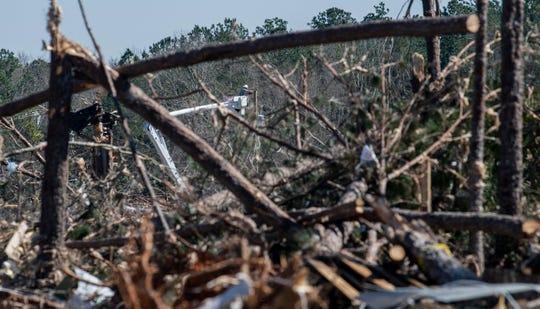 Lineman repair power lines among tornado damage in Beauregard, Ala., on Wednesday March 6, 2019. A fatal tornado struck Beauregard on Sunday afternoon.