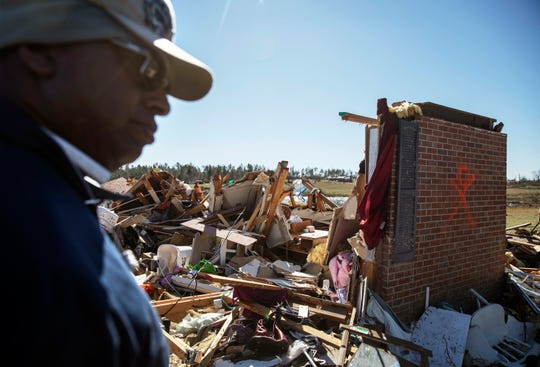 Bernard Reese stands next to the rubble of his aunt's home in which she survived a tornado as he helps retrieve personal items in Beauregard, Ala., Tuesday, March 5, 2019. (AP Photo/David Goldman)