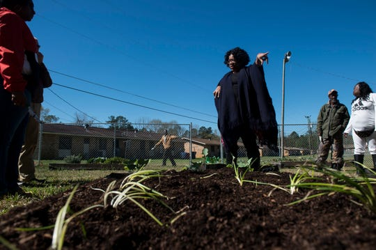 Tana Shealey, Lowndes County Extension Coordinator, helps tenants plant vegetables at the community garden at the Edgewood housing complex in Fort Deposit, Ala., on Wednesday, March 6, 2019.