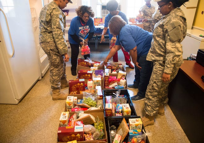Parent Liaison Cubie Rae Hayes with the help of JROTC students loads boxes of foods in the food pantry at Lanier High School in Montgomery, Ala., on Tuesday, March 5, 2019.