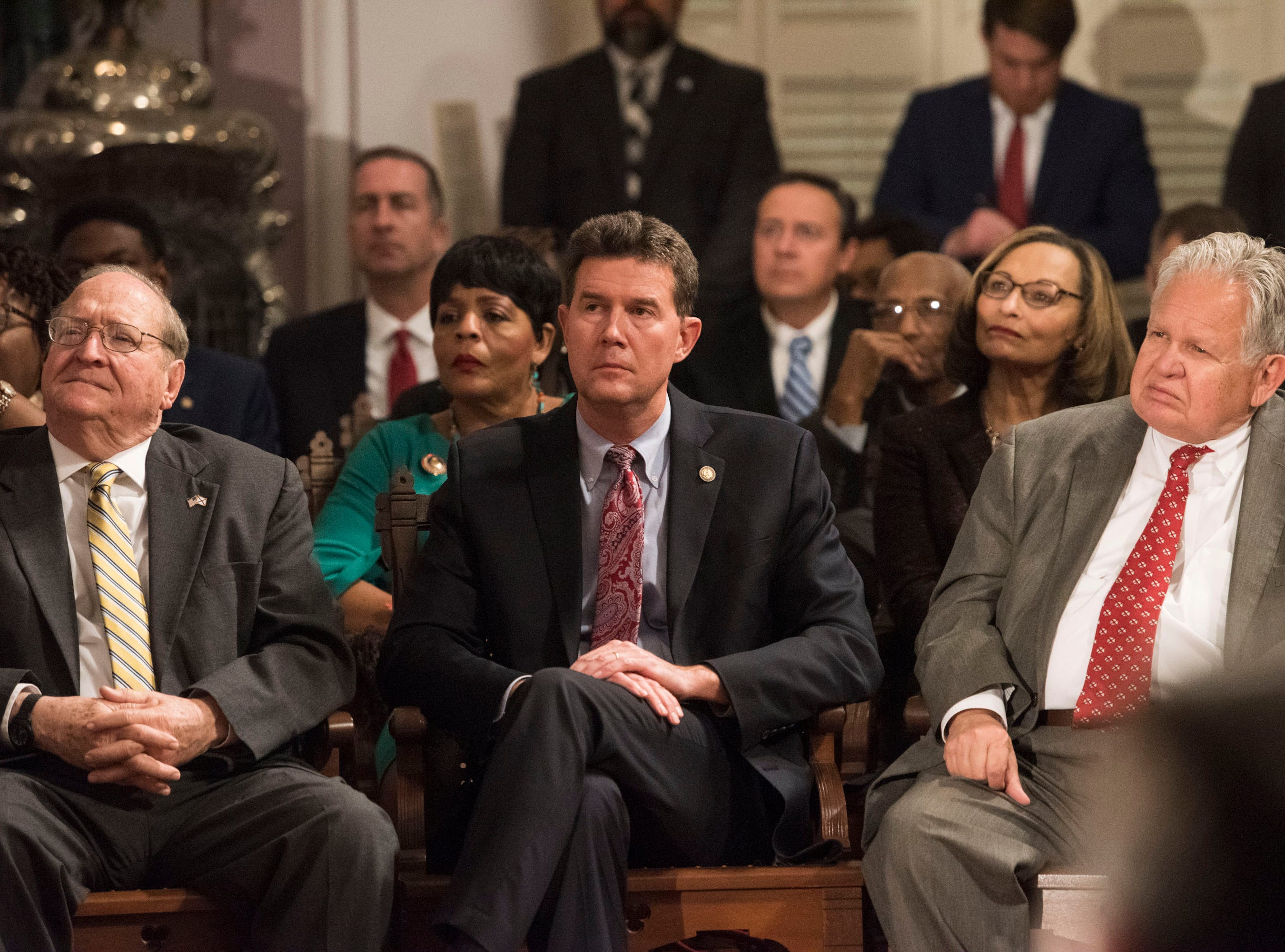 State Treasurer John McMillan, from left, Secretary of State John Merrill and State Auditor Jim Zeigler watch as Gov. Kay Ivey delivers the State of the State address inside the old house chambers at the Alabama State Capitol in Montgomery, Ala., on Tuesday, March 5, 2019.