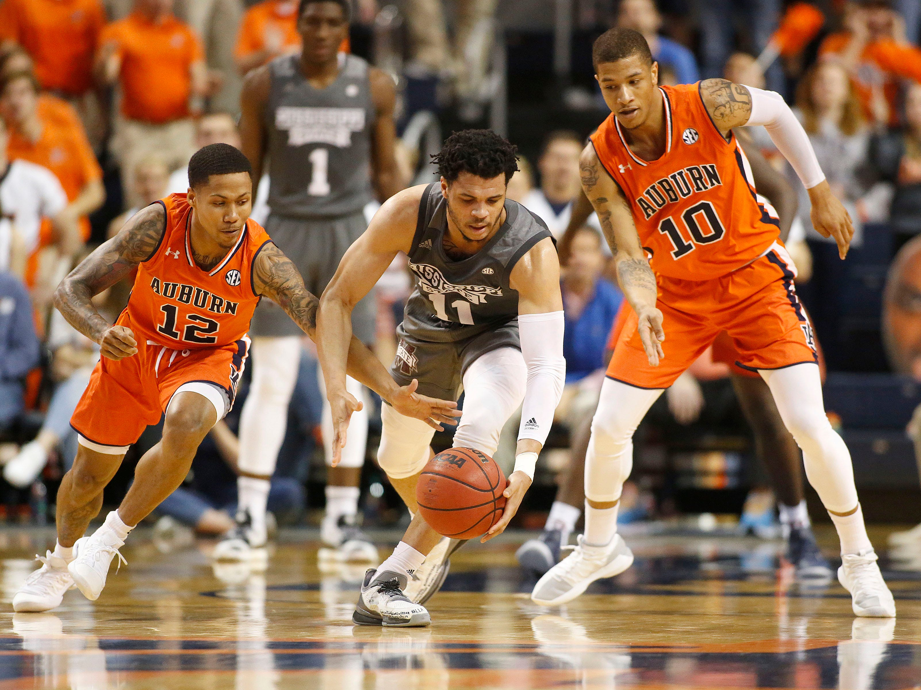 Mar 2, 2019; Auburn, AL, USA; Auburn Tigers guard Samir Doughty (10) and guard J'Von McCormick (12) defend Mississippi State Bulldogs guard Quinndary Weatherspoon (11) during the second half at Auburn Arena. Mandatory Credit: John Reed-USA TODAY Sports