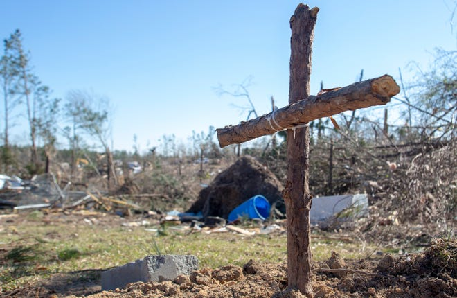 A makeshift cross stands in the yard of a home in Beauregard.