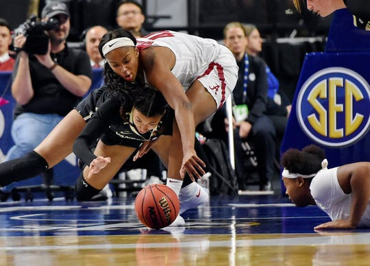 Alabama's Jasmine Walker, top, battles for a loose ball with Vanderbilt's LeaLea Carter, left, during the first half of an SEC tournament game Wednesday.