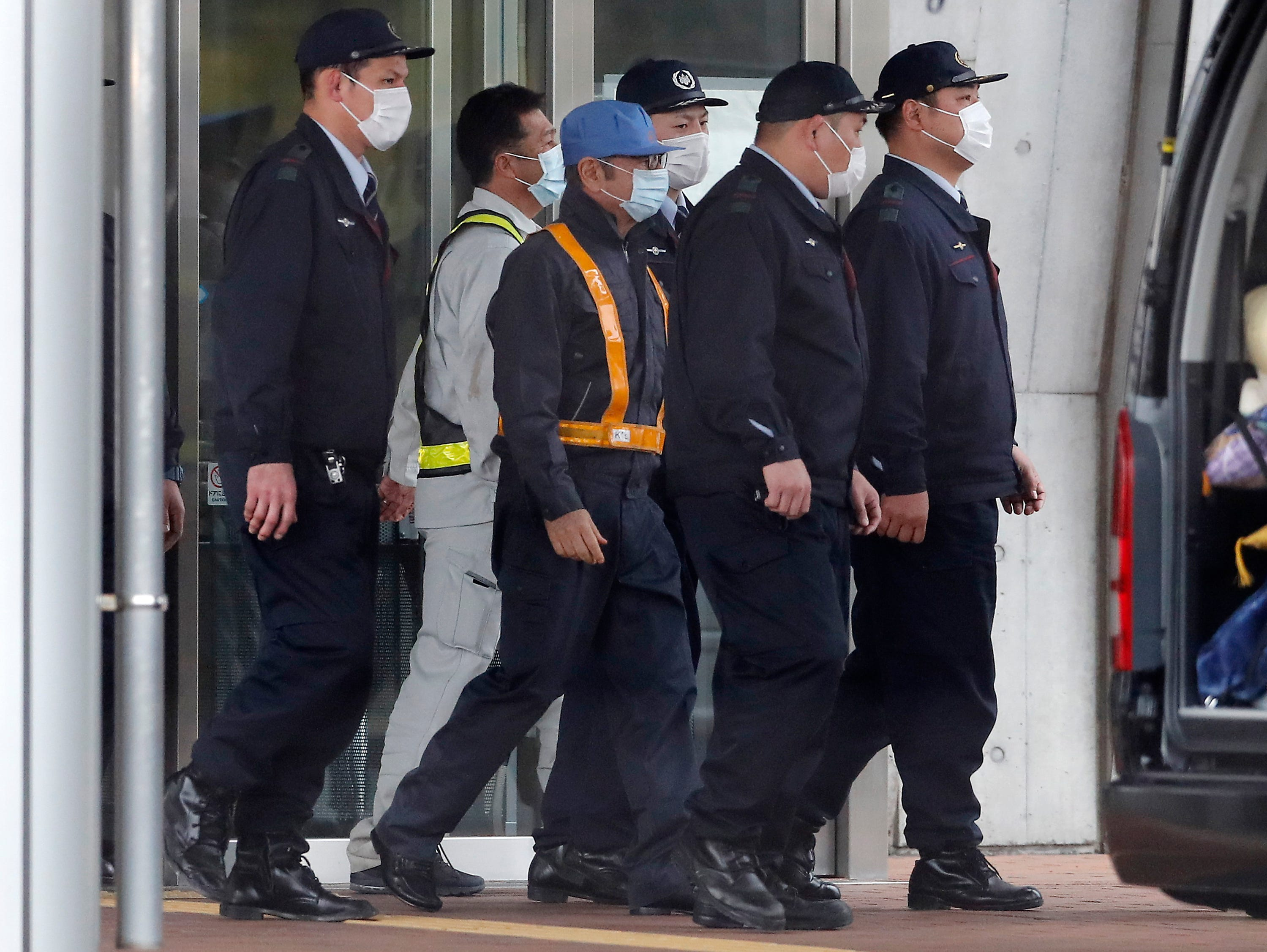 A masked man, center with blue cap, believed to be former Nissan Chairman Carlos Ghosn, walks out with security guards from Tokyo Detention Center in Tokyo Wednesday, March 6, 2019, after posting 1 billion yen ($8.9 million) in bail once an appeal by prosecutors against his release was rejected. (AP Photo/Eugene Hoshiko)
