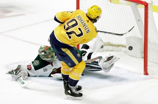 Nashville Predators center Ryan Johansen (92) scores the winning goal against Minnesota Wild goaltender Devan Dubnyk (40) during a shootout in an NHL hockey game Tuesday, March 5, 2019, in Nashville, Tenn. The Predators won 5-4.