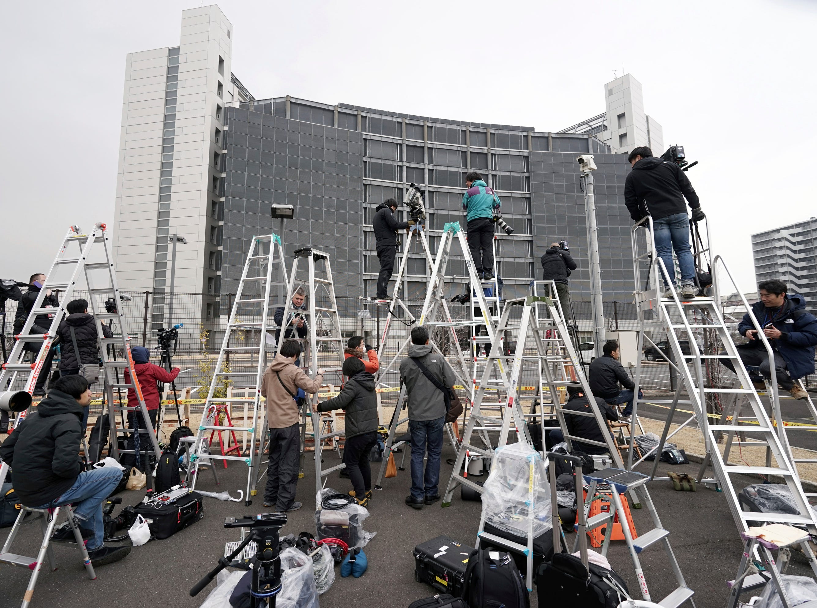 Step ladders placed by photographers and cameramen are seen in front of Tokyo Detention Center, where former Nissan Chairman Carlos Ghosn is detained, Wednesday, March 6, 2019, in Tokyo. (AP Photo/Eugene Hoshiko)