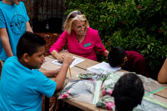 Raynelle Perkins helps Global Gardens students write in their garden journal, where they record the activities they did each day in the garden. Perkins, a member of Naples Garden Club, volunteers weekly with the club in preparation for the Naples Flower Show.