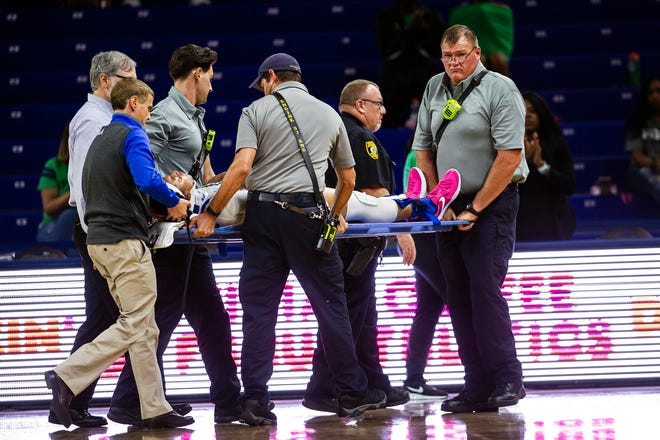 Florida Gulf Coast University's Destiny Washington is taken out during a game against Stetson on Tuesday after a collision under the basket and hitting her head.