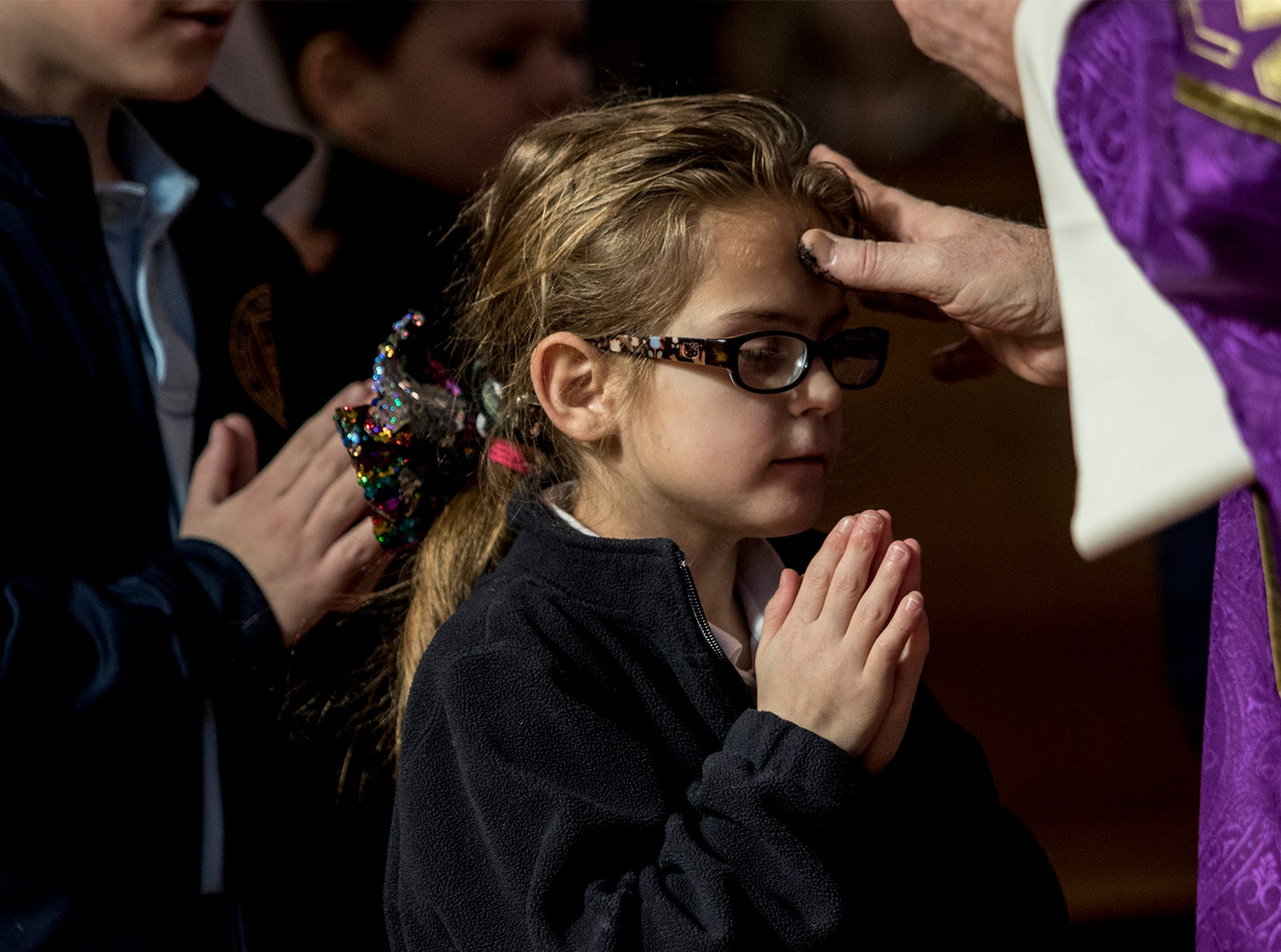 Kylie Clouse, a second grader  from St. Francis De Sales receives ashes on her forehead from Deacon Steve Demers during the Ash Wednesday service.