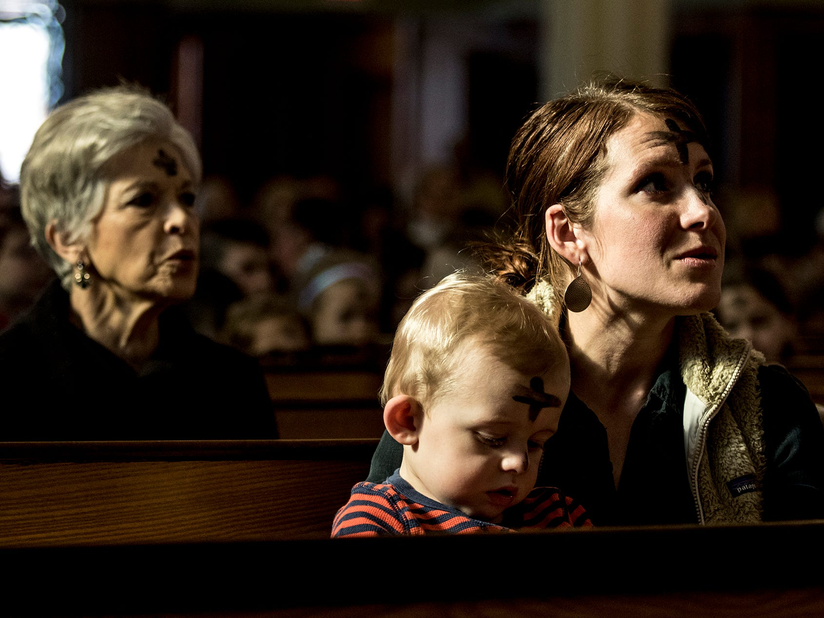 Abigail Rehbeck sings hymns at St, Francis De Sales Church in Newark, with her 2 year old son, Pace, after receiving Ashes for Ash Wednesday. Behind her is Anna Rehl who has been a member of the church for the past 10 years.