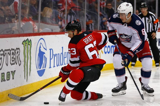 New Jersey Devils left wing Jesper Bratt (63) battles for the puck with Columbus Blue Jackets defenseman Zach Werenski (8) during the second period of an NHL hockey game Tuesday, March 5, 2019, in Newark, N.J.