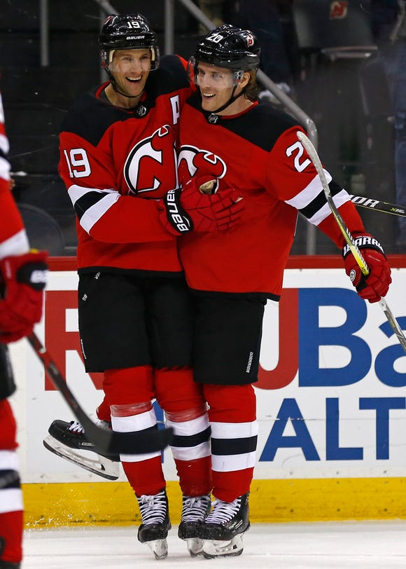 New Jersey Devils center Travis Zajac (19) celebrates scoring a goal with Blake Coleman (20) during the second period of an NHL hockey game against the Columbus Blue Jackets on Tuesday, March 5, 2019, in Newark, N.J.