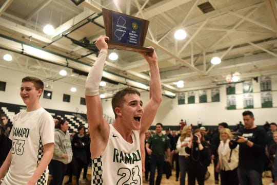 Ramapo High School defeated Teaneck High School 65-40 in the NJSIAA North 1, Group 3 boys basketball final on Tuesday, March 5, 2019 in Franklin Lakes.  Kyle Hroncich #23 hoists the team's trophy into the air.