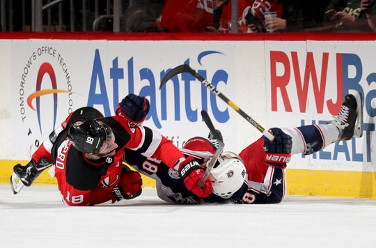 NEWARK, NEW JERSEY - MARCH 05:   Drew Stafford #18 of the New Jersey Devils and Boone Jenner #38 of the Columbus Blue Jackets collide in the second period on March 05, 2019 at Prudential Center in Newark, New Jersey