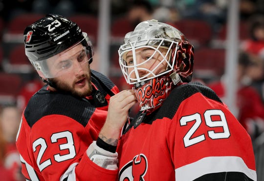 Stefan Noesen (23) of the New Jersey Devils helps teammate Mackenzie Blackwood (29) of the New Jersey Devils with his mask during warm ups before the game against the Columbus Blue Jackets on March 5, 2019 at Prudential Center in Newark, New Jersey.