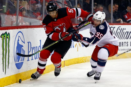 New Jersey Devils defenseman Connor Carrick (5) battles for the puck with Columbus Blue Jackets center Matt Duchene (95) during the first period of an NHL hockey game Tuesday, March 5, 2019, in Newark, N.J.