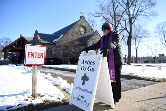 """Priest Tom Matthews sets up an """"Ashes To Go,"""" placard at the entrance of the drive-thru on Ash Wednesday at Christ Episcopal Church in Ridgewood on March 6, 2019."""