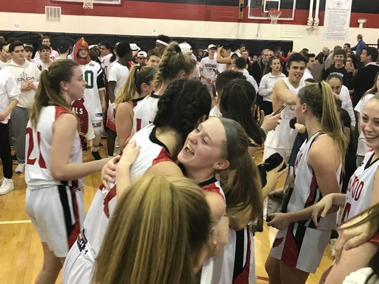Westwood senior Rachel Bussanich gets a hug from teammate Kate Dobson after the Cardinals defeated Newton, 43-38, in the North 1, Group 2 girls basketball final on Tuesday, March 5, 2019.