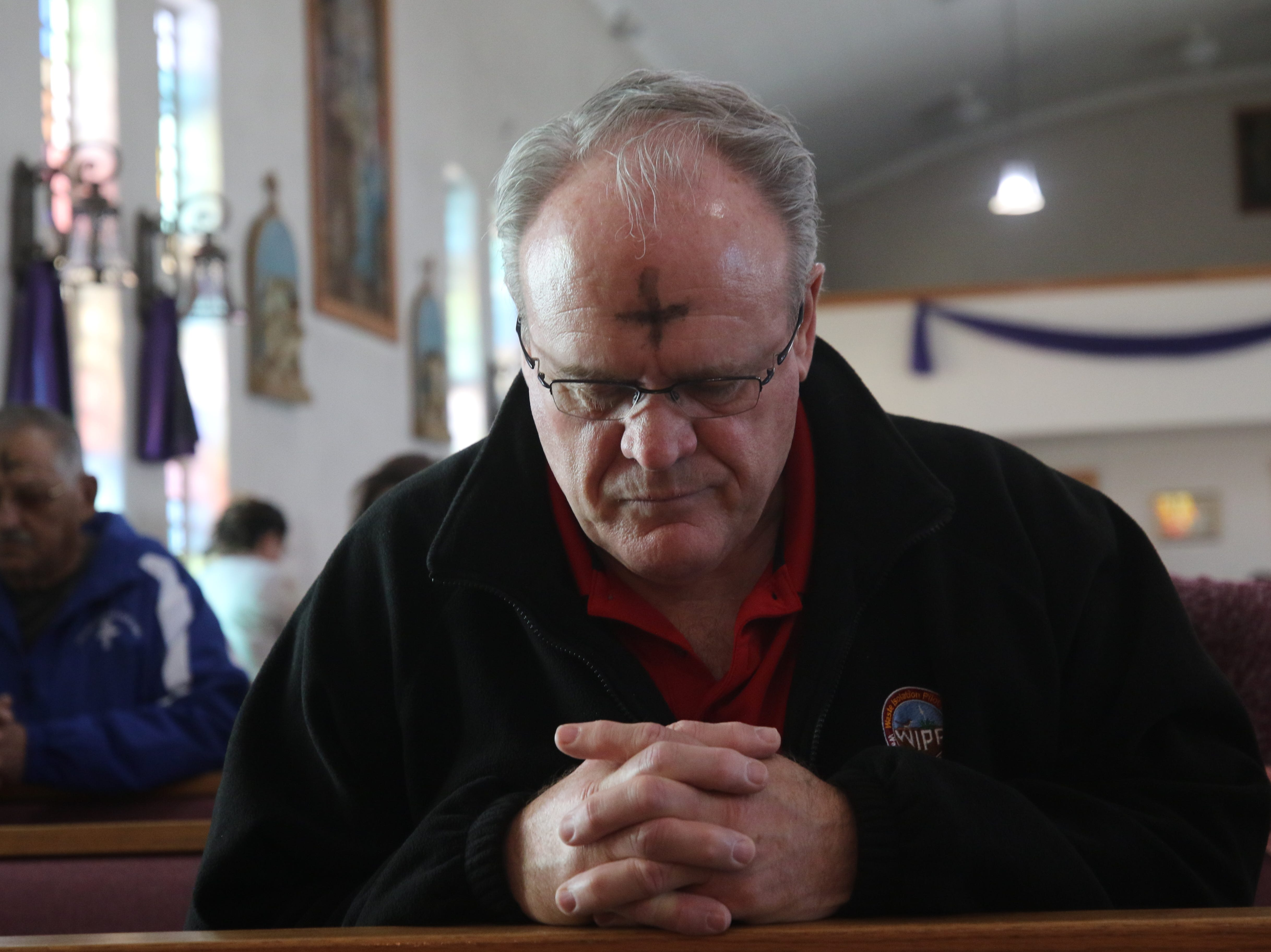 After getting their ashes, attendees engage in prayer at an Ash Wednesday mass, March 6, 2019 at St Edward Catholic Church.