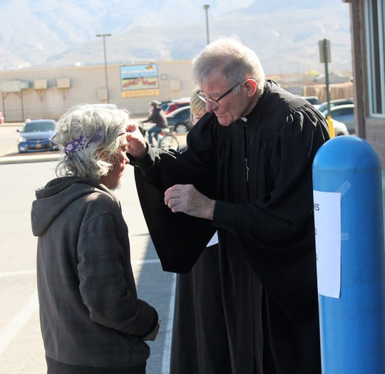 Pastor Mike Degner of Our Savior Lutheran Church in Alamogordo places ashes on a Wal-Mart customer.
