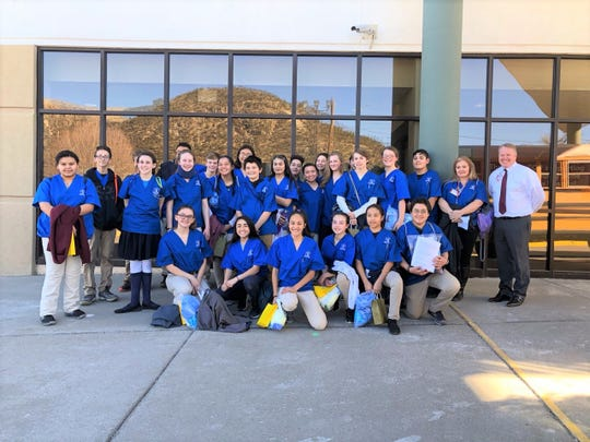 Ruidoso Middle school students and Lincoln County Medical Center chief hospital director Todd Oberheu take time out during MASH Camp for a picture in front of the hospital's entrance.