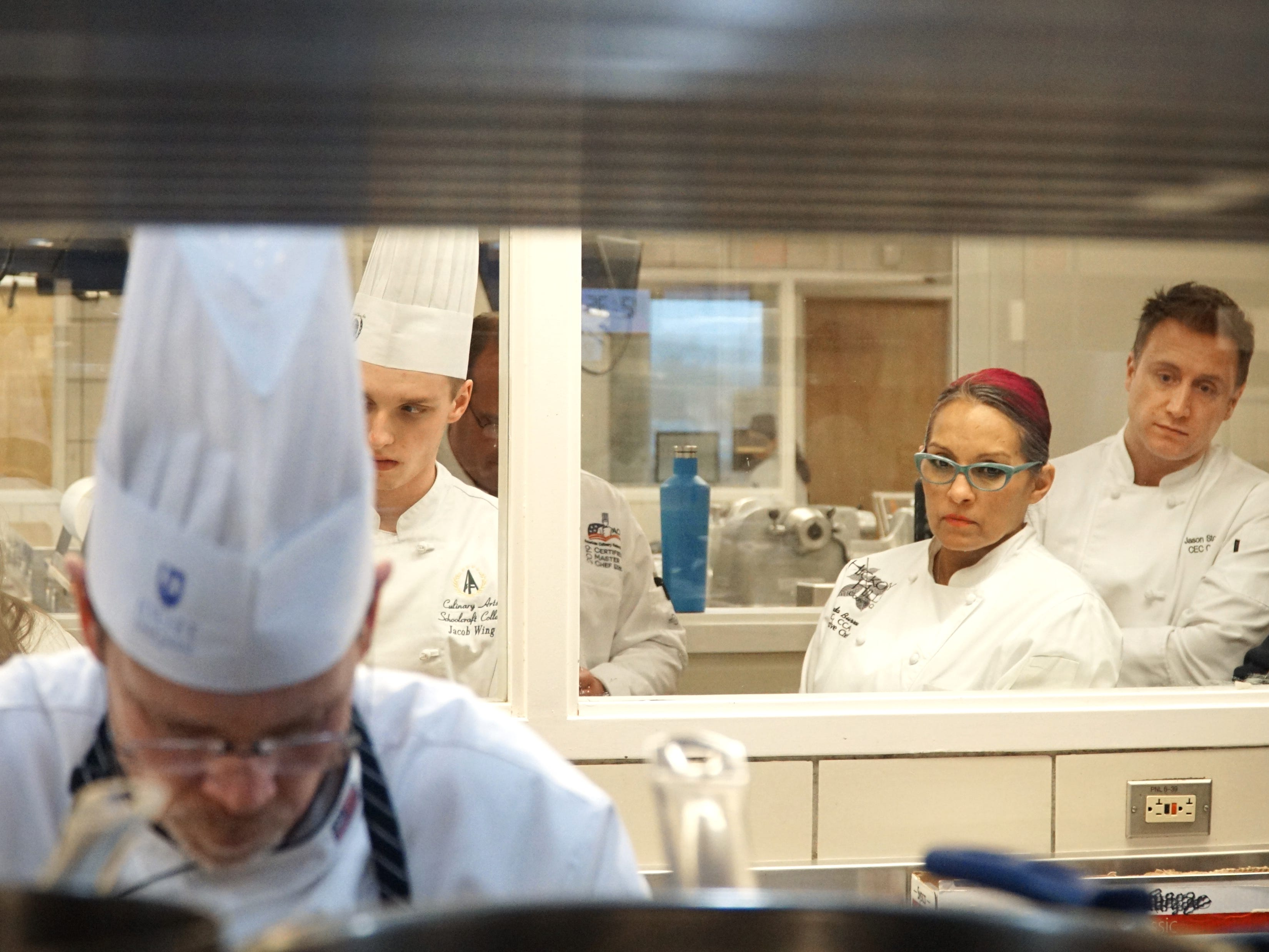 Certified Master Chef exam student Timothy Bucci, center-left, is watched by a window-ful of other chefs from Schoolcraft College and around the country as he makes his meal.  Melinda Burrows, second from right, came from Springfield, Missouri to judge the student.