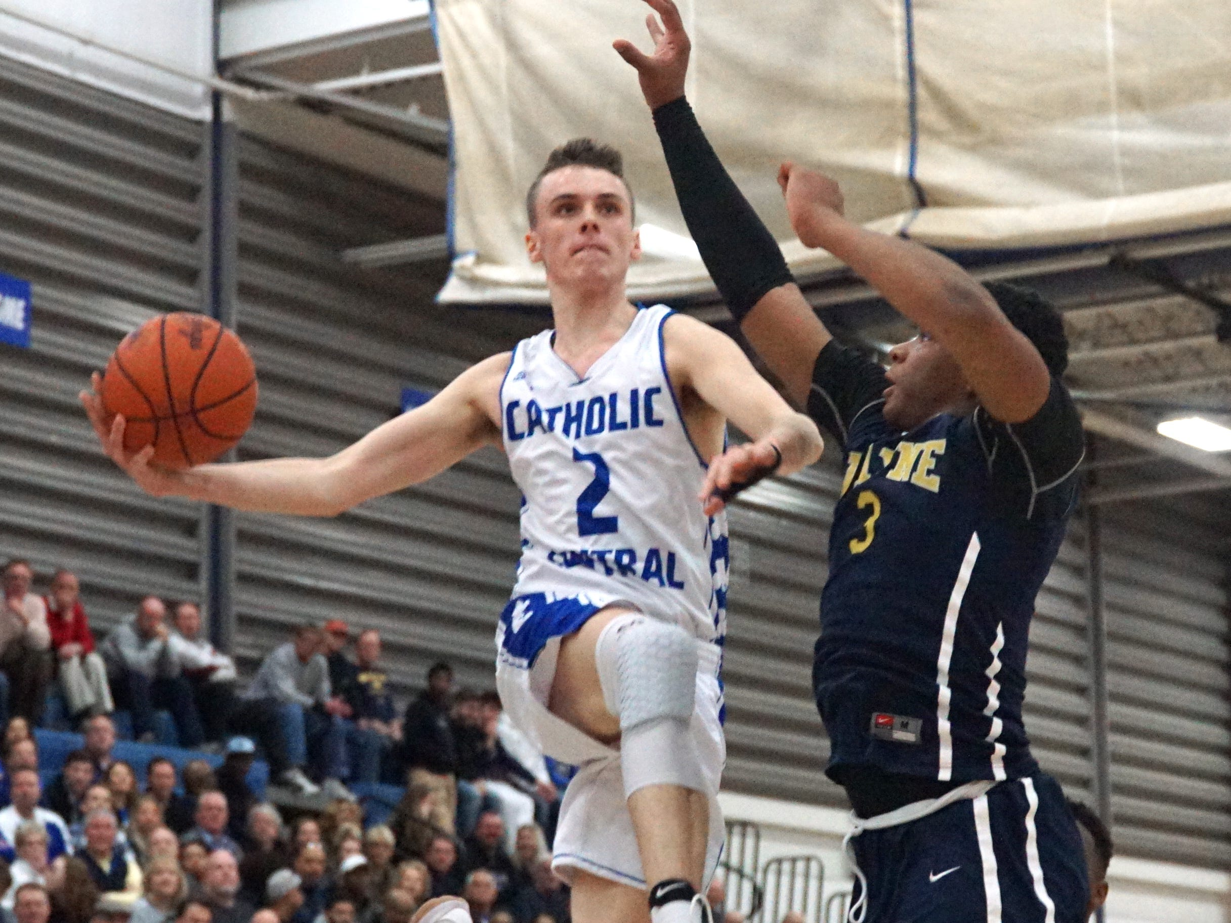 Detroit Catholic Central's Brendan Downs' Michael Jordan-esque leap from the baseline towards the net got an appreciative wow from the crowd. Cartier Muse-Suber, right, tries to defend the Shamrock.