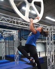 While dangling in the air - Sophie Shaft works on moving a wheel over a bar by her own momentum