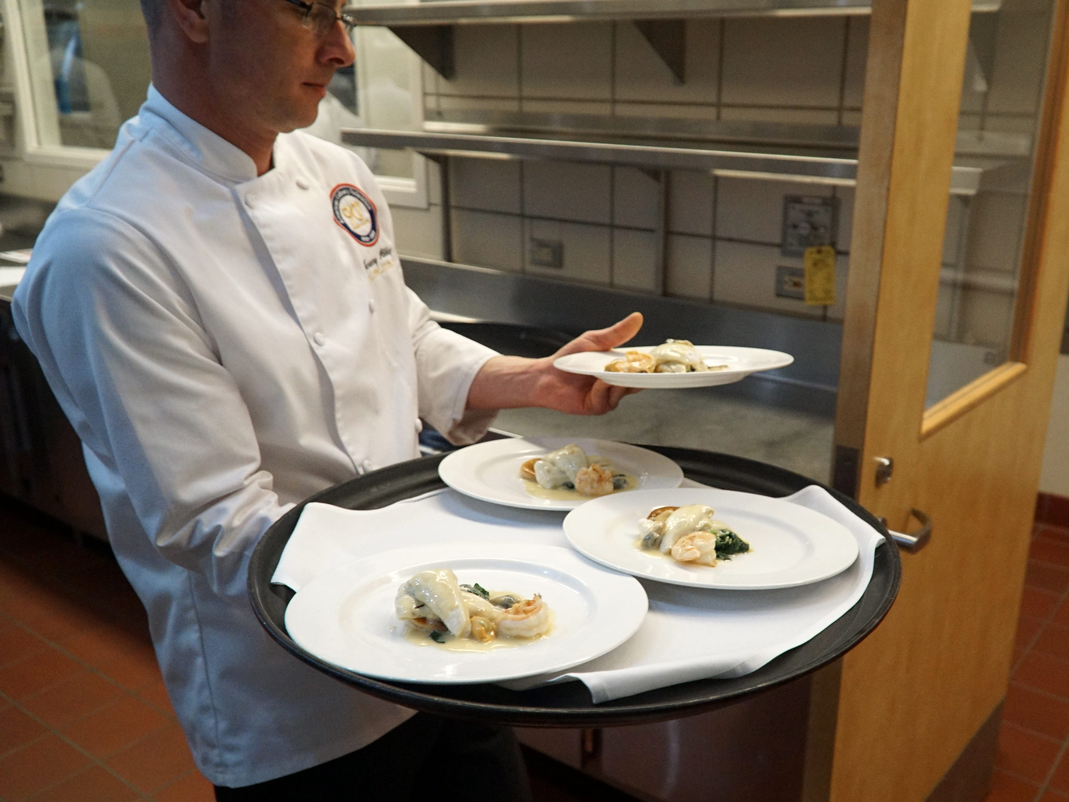 Bucci's filet of sole with shrimp and wilted spinach heads out to be tasted.