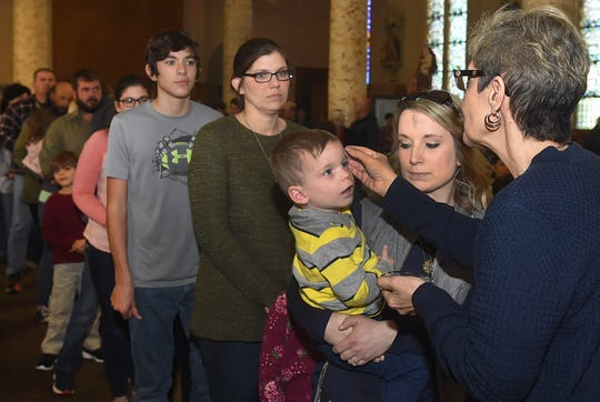 Lay Minister Nelda Villery administers Holy Ashes onto the forehead of a young parishoner during Ash Wednesday services at St. Landry Catholic Church. See more photos of the service at dailyworld.com and on the Daily Word Facebook site.