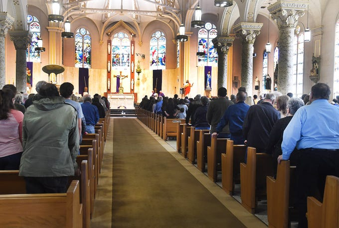 Monsignor Russell J. Harrington celebrates Holy Mass and the distribution of Holy Ashes during Ash Wednesday services at St. Landry Catholic Church.