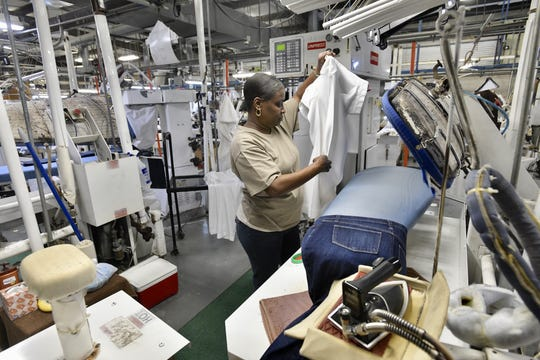 Keyna Simpson, an employee at Vick's Cleaners, presses laundry at the Pensacola business on Wednesday.