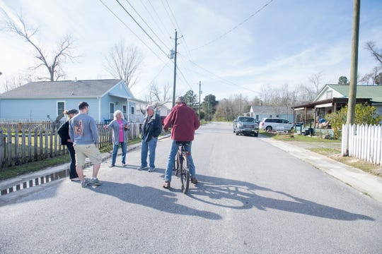 From left, residents Shea Rozier, Josh Rozier, Rose Wilson, Willie Wilson and Randy Coker chat along Front Street in Century on Wednesday.