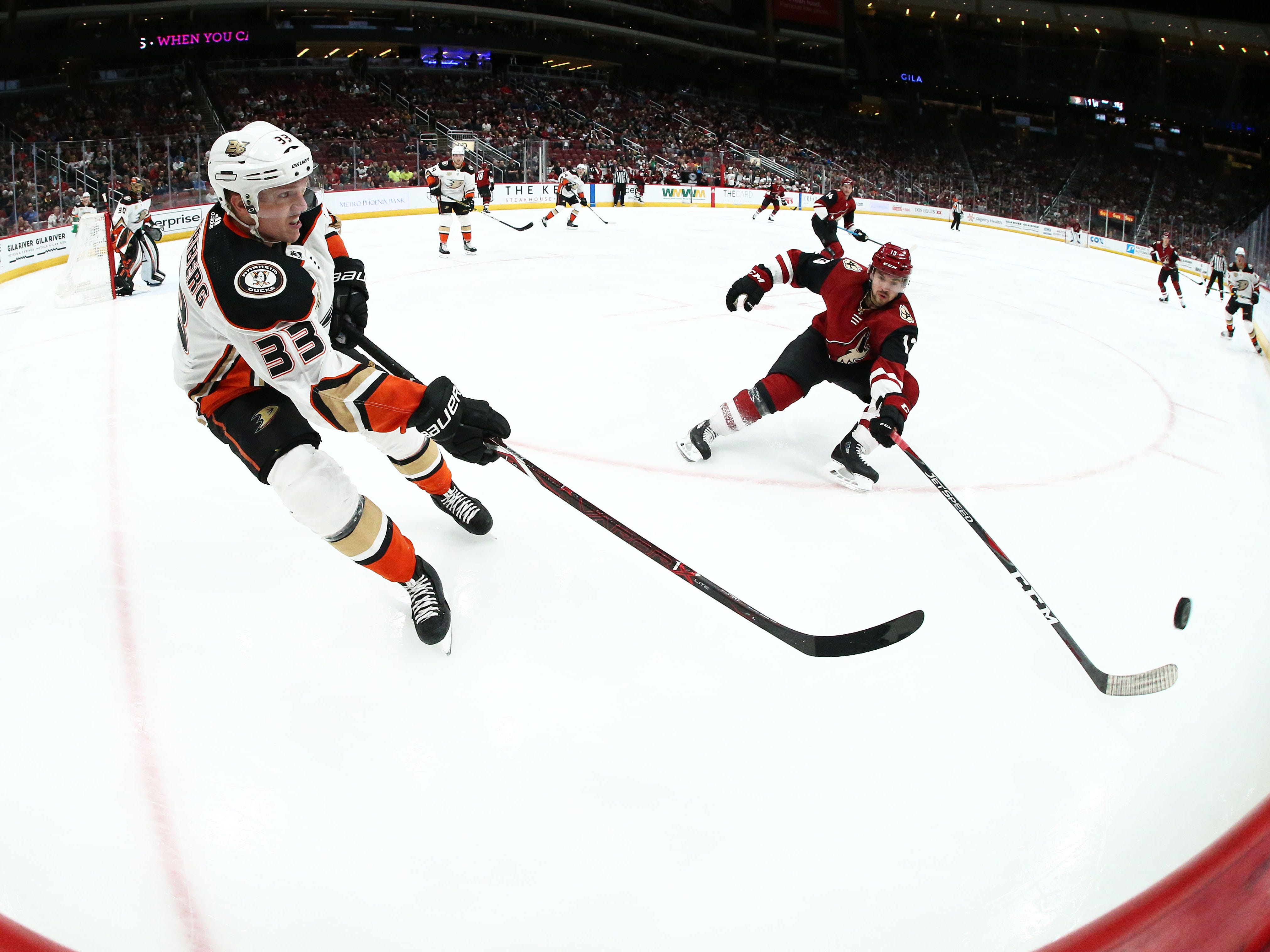 Anaheim Ducks right wing Jakob Silfverberg (33) passes the puck against Arizona Coyotes center Vinnie Hinostroza (13) in the second period on Mar. 5, 2019, at Gila River Arena in Glendale, Ariz.