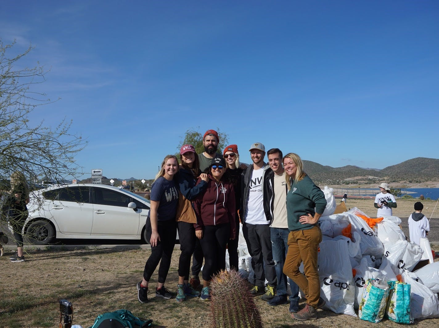 (Left to Right) Keep Nature Wild staff Gillian Coyle, Cassie Jarman, Sean Huntington, Shawni Huntington, Cameron Jarman, Blake Curry, Melissa Wright and Joanna Fiorentino pose for a photo with the pile of trash collected by volunteers at a cleanup day at Lake Pleasant on Nov. 23, 2018.