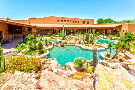 The Scottsdale estate purchased by David and Linda Durbano, includes a pool bordered with desert landscape.