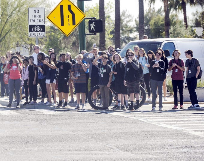 Phoenix students salute Vice President Mike Pence's motorcade as it leaves Phoenix on March 5, 2019.