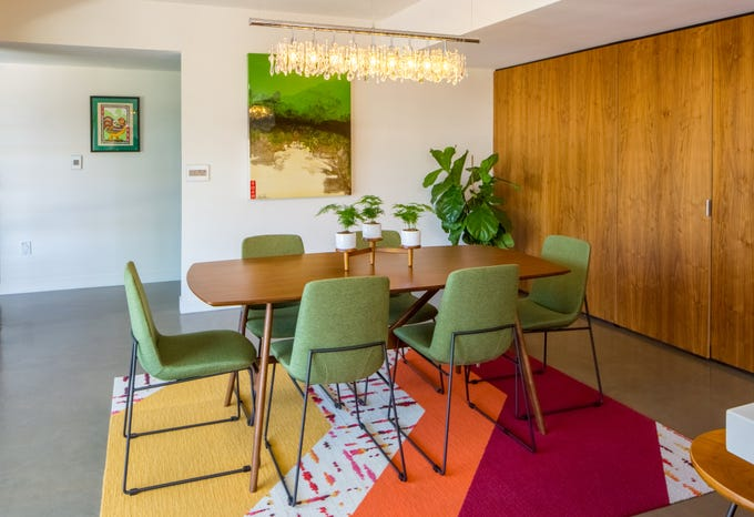 This dining table features midcentury legs and is complemented with modern upholstered chairs in chartreuse, one of the signature colors of midcentury homes.