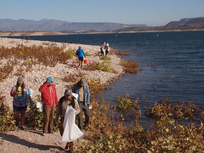 Volunteers search for trash along the shoreline of Lake Pleasant on Nov. 23, 2018.
