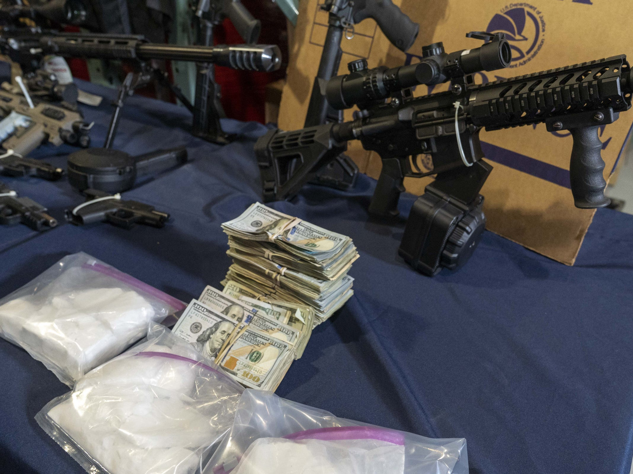DEA agents show stored drugs, weapons and cash at a facility in the Phoenix area on March 5, 2019.