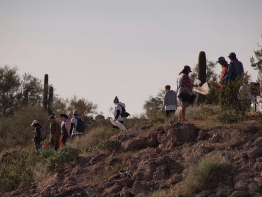 Volunteers scan the area for trash on the hike down to the shoreline of Lake Pleasant on Nov. 23, 2018 for Keep Nature Wild's Impact Friday cleanup.