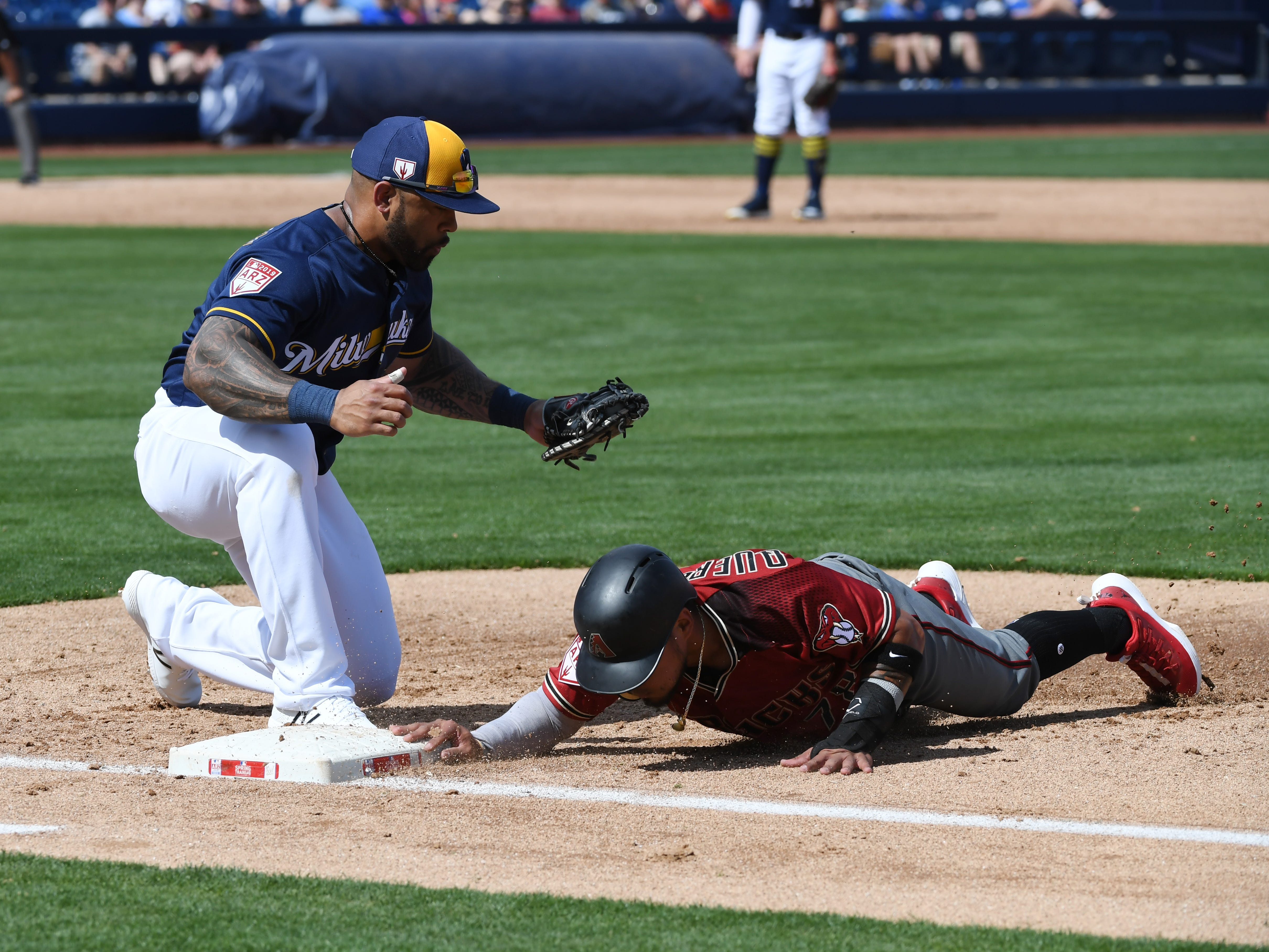 Juniel Querecuto #78 of the Arizona Diamondbacks safely dives back to first base as Eric Thames #7 of the Milwaukee Brewers applies a tag during the third inning of a spring training game at Maryvale Baseball Park on March 06, 2019 in Phoenix, Arizona.