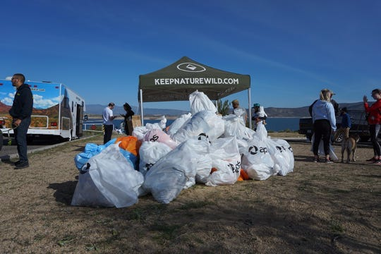A growing pile of trash bags filled by volunteers at the end of the cleanup at Lake Pleasant on Nov. 23, 2018.