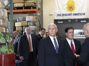 Vice President Mike Pence and Gov. Doug Ducey, listen to a DEA agent at a covert facility in the Phoenix area during the tour on March 5, 2019.