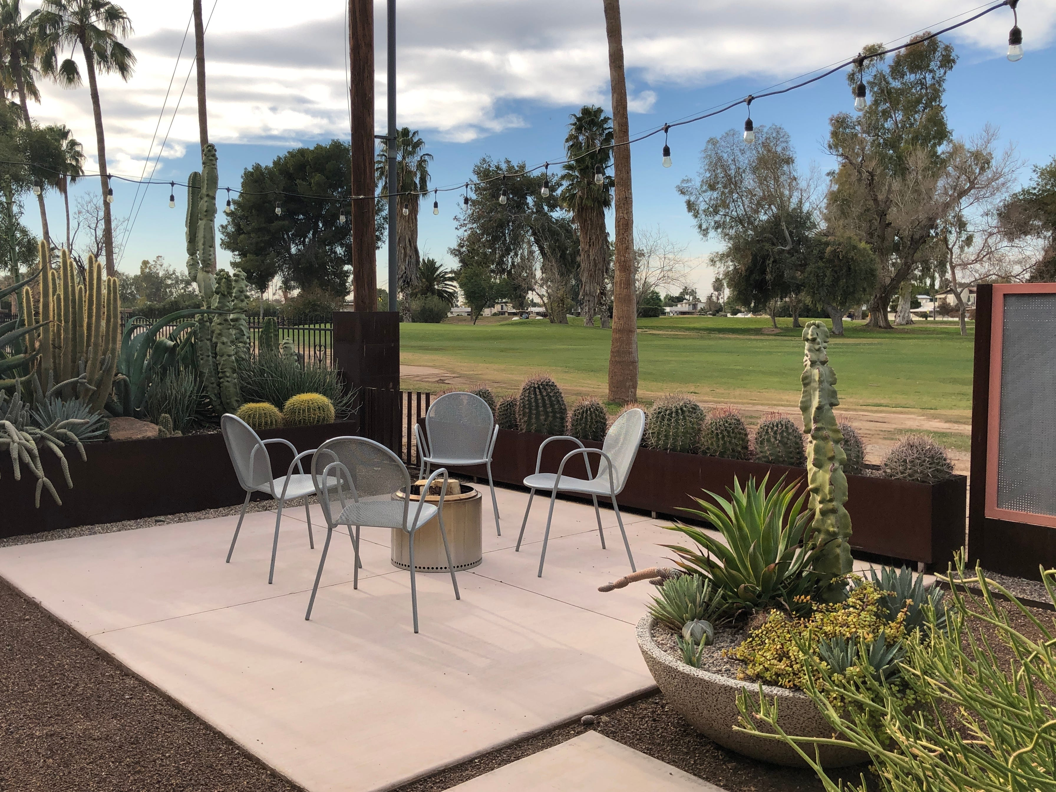 Succulents and other desert foliage create a cozy and low-maintenance environment amid a golf-course backdrop.