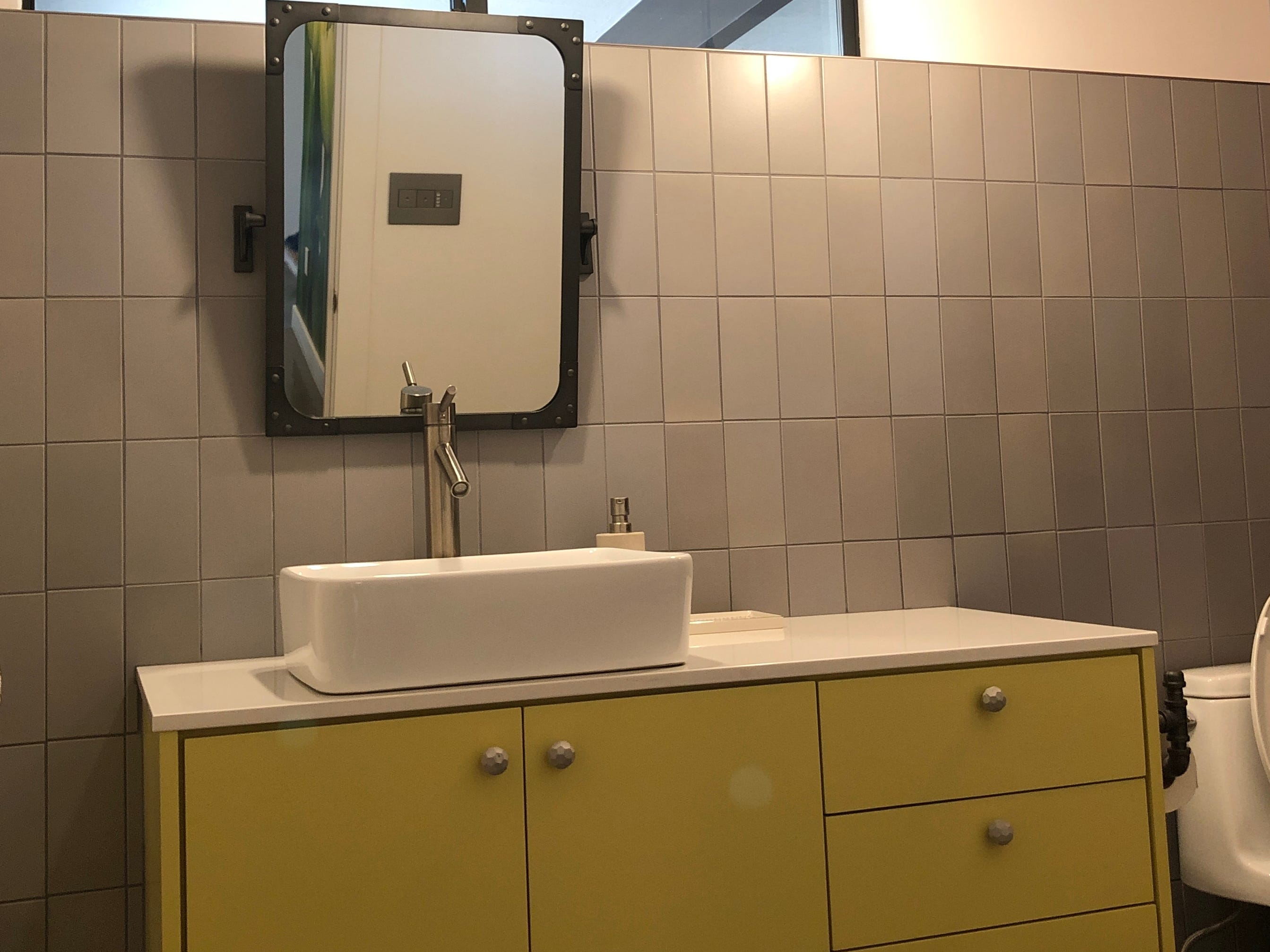 Both bathrooms were completely remodeled, including the guest bath, which Vierra's son uses. Vierra installed this sink with yellow cabinets and quartz countertops.