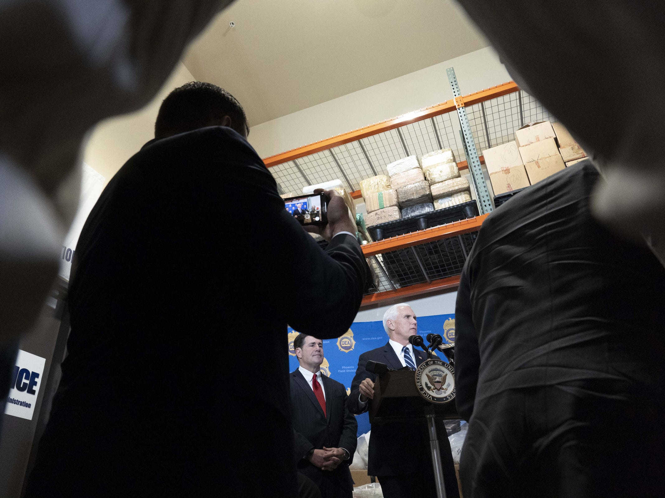 Vice President Mike Pence and Gov. Doug Ducey watch as DEA agents show stored drugs, weapons and cash at a facility in the Phoenix area during a tour on March 5, 2019.
